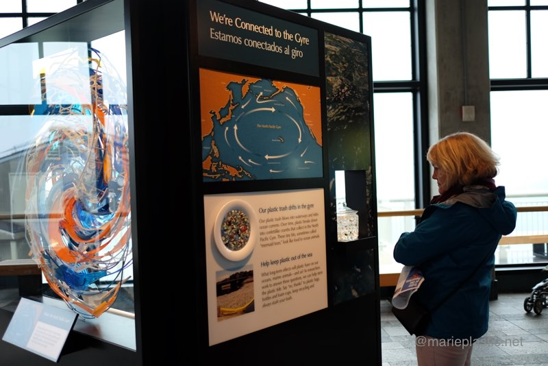 モントレー水族館でのプラスチック問題の説明パネルを見る女性