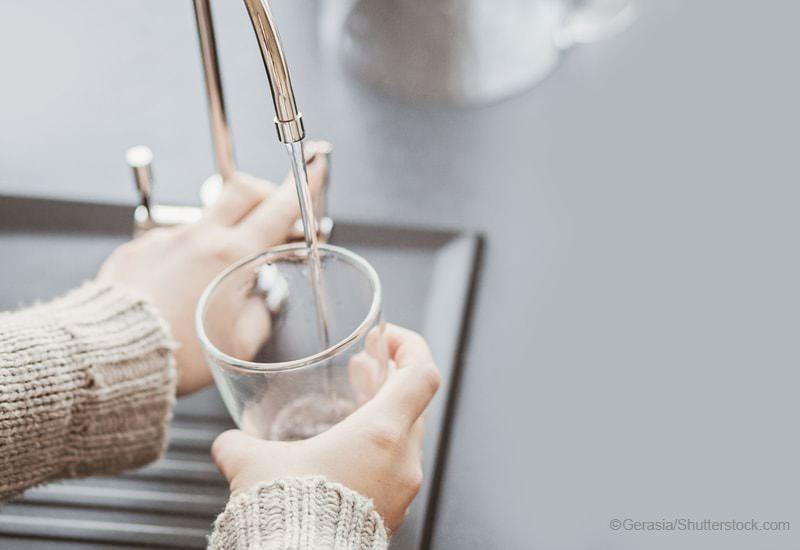 ガラスコップに水を入れる女性