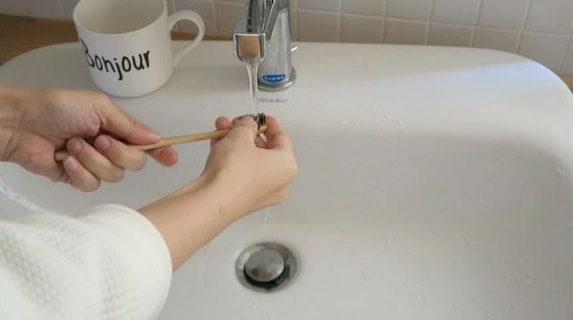 歯ブラシを水で洗う様子