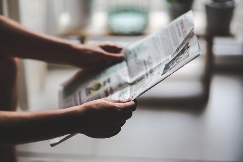 新聞を眺める人