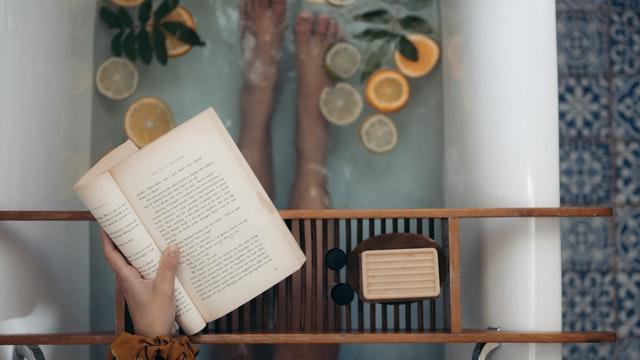 本を読みながら入浴している女性の脚