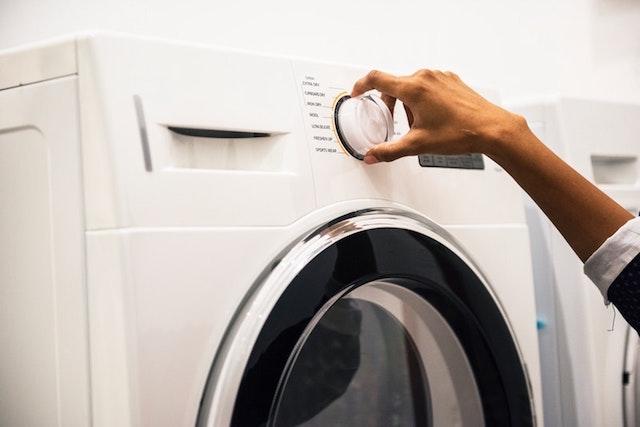 洗濯機のダイヤルを回す手