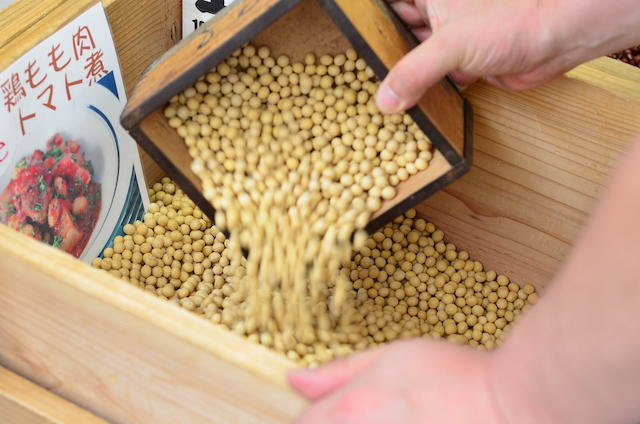 枡で豆をすくっている様子