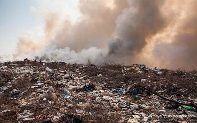 プラスチックごみの山から立ち上る煙
