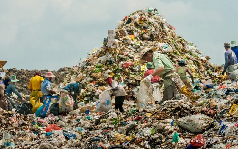 プラスチックごみの山で作業する男性たち
