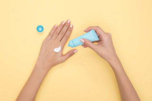 化粧クリームを手に塗る女性