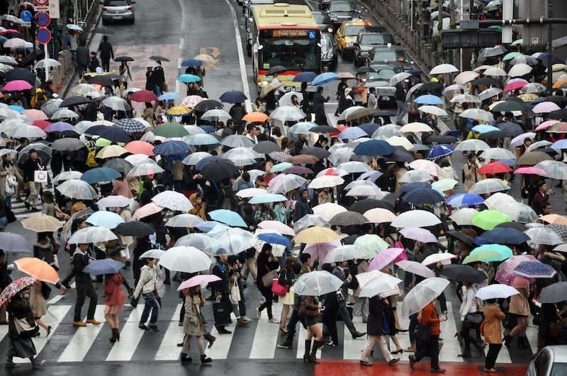 傘をさして交差点を横断する群衆