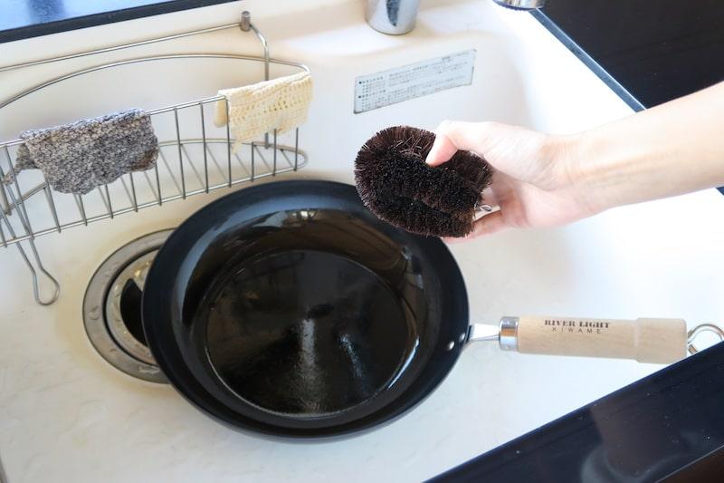 水とタワシで鉄フライパンを洗う様子