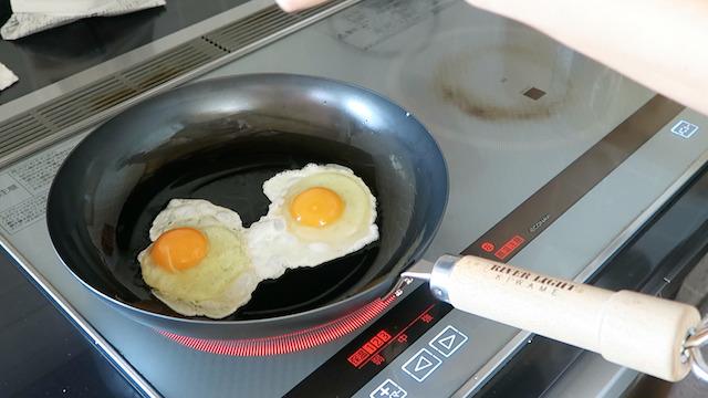 熱した鉄フライパンに卵を割り入れる様子