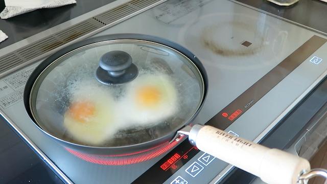 鉄フライパンに蓋をして卵を焼く様子