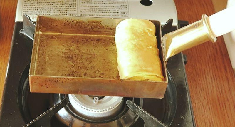 銅の玉子焼き器で卵焼きを焼く様子