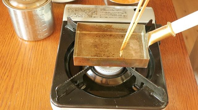 卵液を少し垂らして焼け具合を確かめるようす