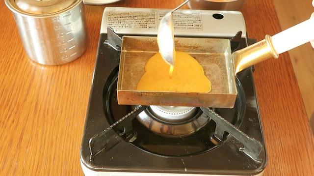 玉子焼き器に卵液を注ぎ入れる様子