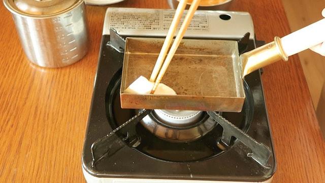 温めた玉子焼き器にキッチンペーパーで油をなじませるようす