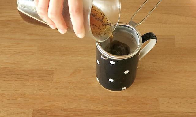 茶こしをセットしたカップにコーヒーを注ぐ様子