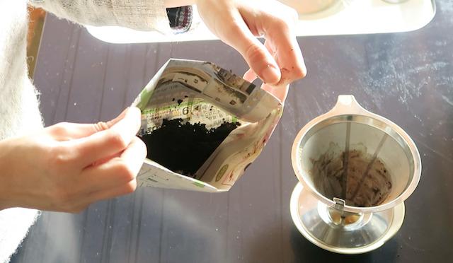 新聞紙ゴミ袋にコーヒーかすを入れる様子