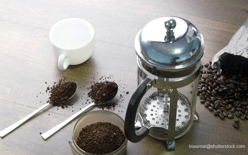 テーブルの上のフレンチプレスとコーヒーの粉