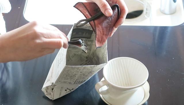 柿渋リネンフィルターからコーヒーかすをスプーンで出す様子