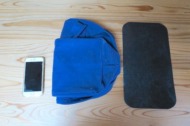 底板をとって折りたたんだバッグとスマホのサイズを比較する様子