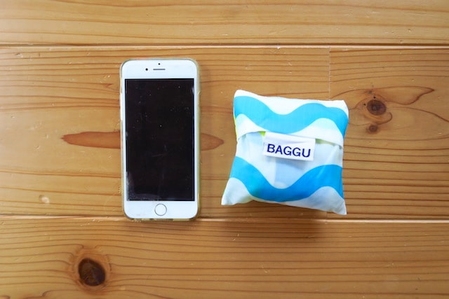 折りたたんだBAGGUとスマホのサイズを比較する様子