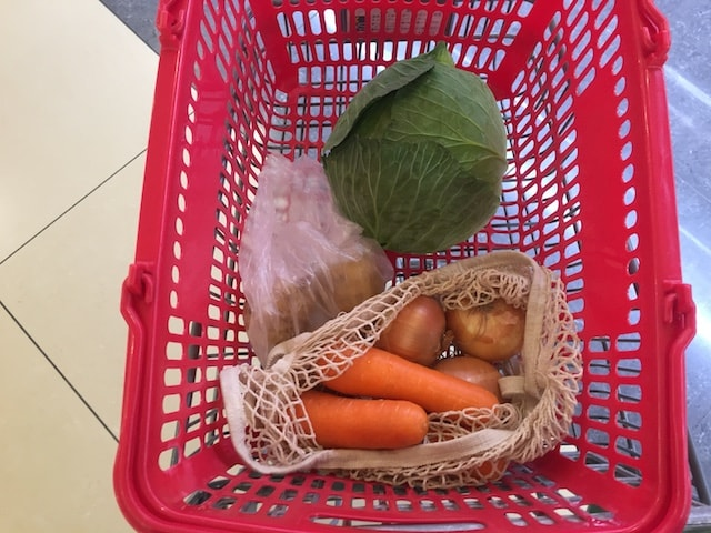 持参したビニール袋にジャガイモを入れて買い物する様子