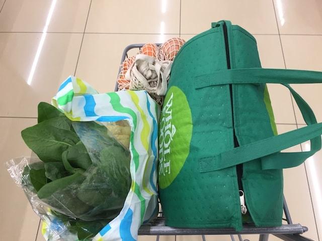 スーパーのカートにファスナーを閉めたホールフーズのエコバッグを乗せて運ぶ様子