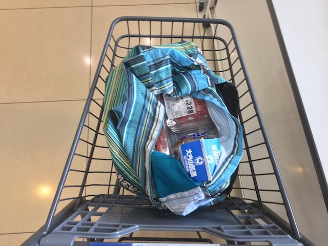商品の入ったラブバッグズをスーパーのカートに乗せて運ぶ様子