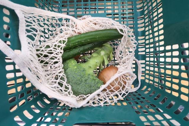 レジカゴの中に置いたメッシュバッグにばら売り野菜を入れる様子