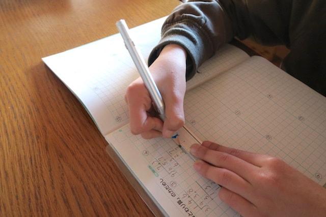 ペンシルホルダーを装着した鉛筆を使って子供が宿題をする様子