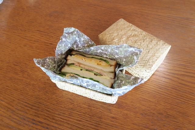 ミツロウラップで包んだサンドイッチを竹かごに入れた様子