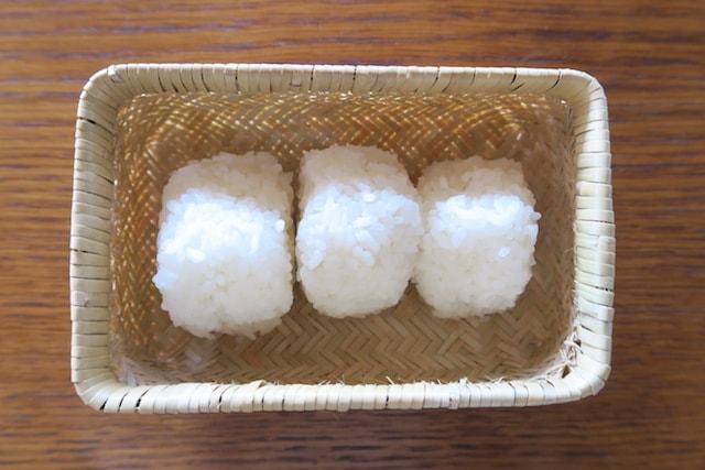 塩むすびを3つ入れた竹かご