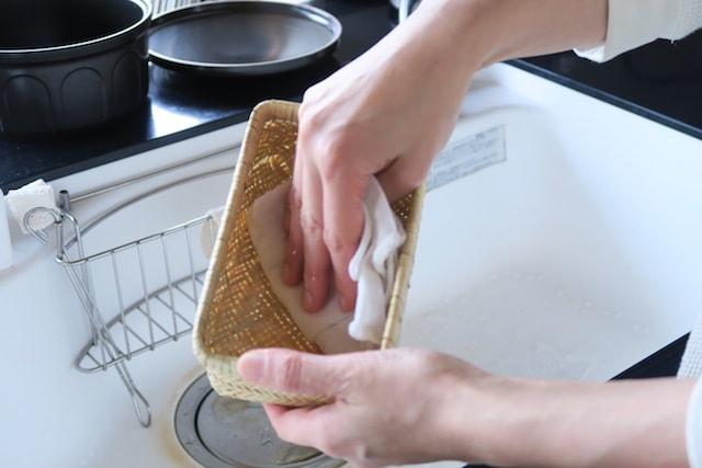 竹かご弁当箱を濡らした布で拭く様子