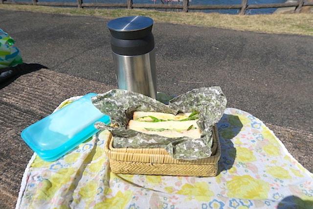 公園のベンチに置いた竹かごと水筒とおしぼり
