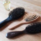 2つの天然毛のヘアブラシと竹ピンブラシと瓶に入った椿油