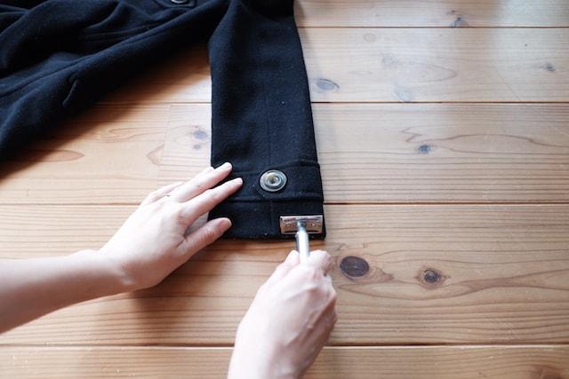 T字カミソリをコートの袖口に当てるようす