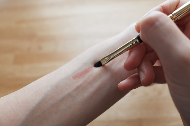 腕の内側に口紅のついたリップブラシで線を引く様子
