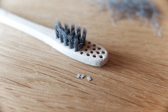 毛を抜いた竹歯ブラシと金属のチップ