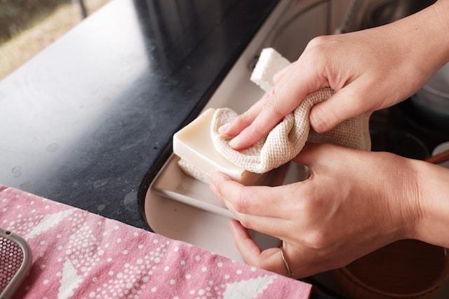 綿のふきんに食器洗い石鹸を擦り付けている様子