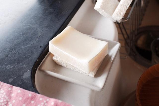 食器洗い石鹸の下にセルローススポンジを敷き、陶器のトレーに乗せている様子