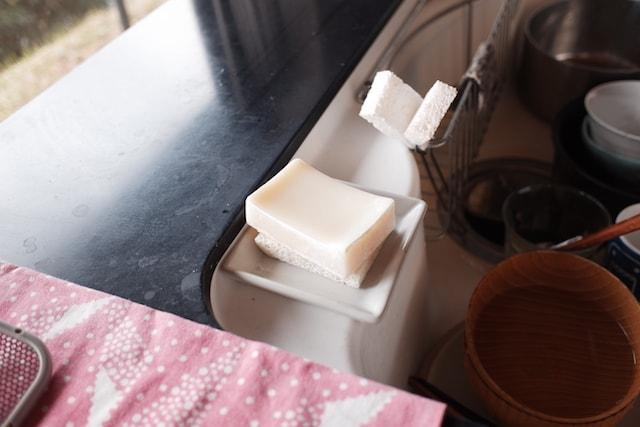 シンクに置いた陶器のトレーに乗せた食器洗い石鹸