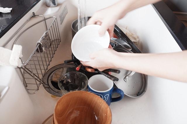 石鹸で洗った食器を流水ですすぐ様子