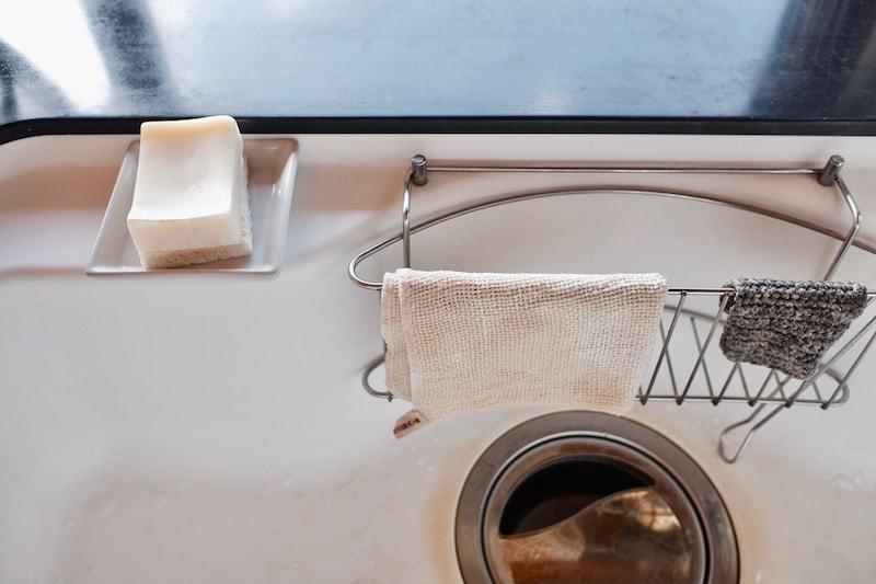 シンクに置いた食器洗い石鹸と綿のふきん