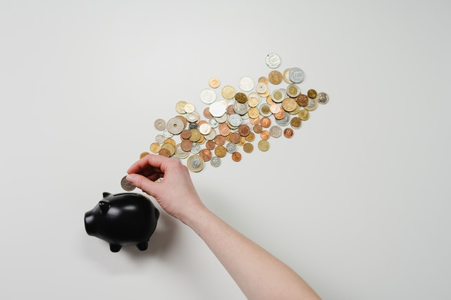 豚の貯金箱にコインを入れる女性の手元
