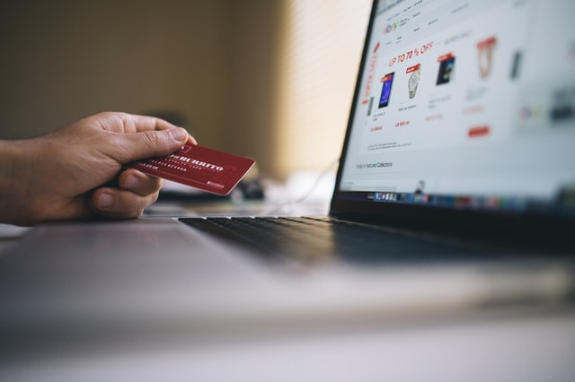 クレジットカードを手に持ってパソコンでネットショッピングをする女性