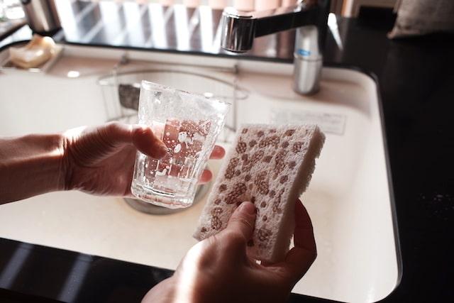 ポップアップスポンジと泡がついたガラスのコップ