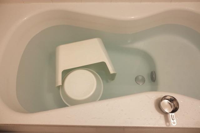 重曹を入れた残り湯に洗面器と椅子をつけている様子