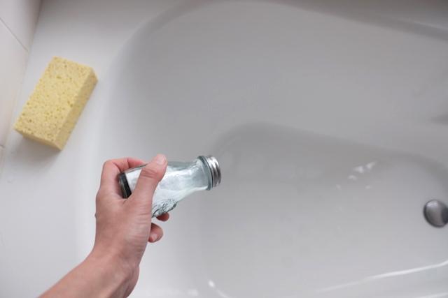 浴槽に重曹の粉をふりかけている様子