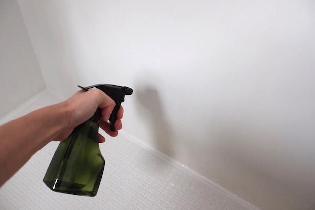 壁の石鹸カスにクエン酸スプレーを吹きかけている様子