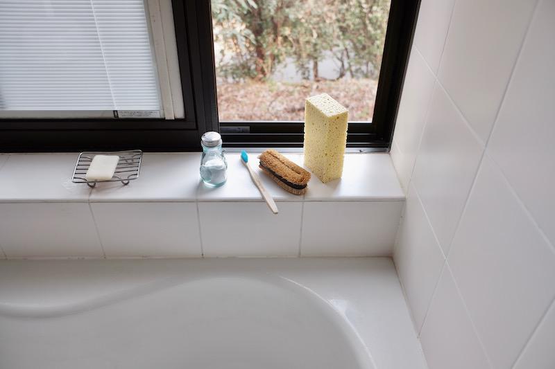 お風呂場の窓辺にセルローススポンジやタワシが並んでおいてある様子