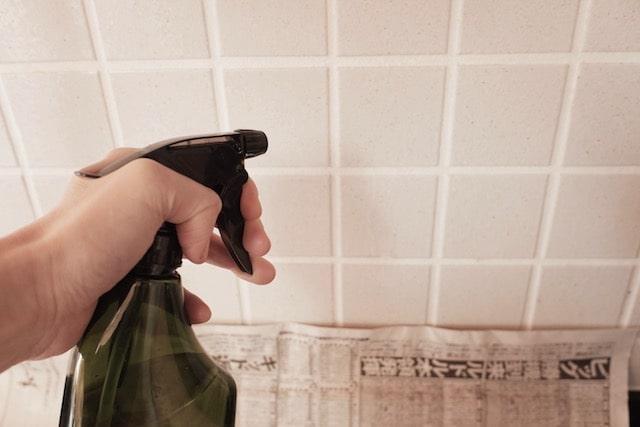 壁の油汚れに重曹スプレーを吹きかけている様子